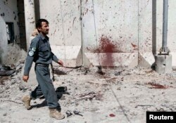 FILE - An Afghan policeman walks past a bloodstained wall after Taliban fighters stormed a government compound in Kandahar province, July 9, 2014.