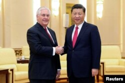 FILE - Chinese President Xi Jinping shakes hands with U.S. Secretary of State Rex Tillerson before their meeting at at the Great Hall of the People in Beijing, China, March 19, 2017.