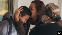 A Sparks Middle School student cries and is comforted after being released from Agnes Risley Elementary School, where some students were evacuated to after a shooting at the school in Sparks, Nevada, Oct. 21, 2013.