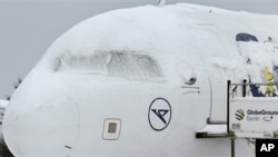 A snow covered aircraft is parked on the airfield at Berlin's Schoenefeld airport in Berlin, Germany, Monday, Dec. 20, 2010. Snow and freezing temperatures continued to cause holiday travel problems Monday for road, rail and air passengers all over Europe