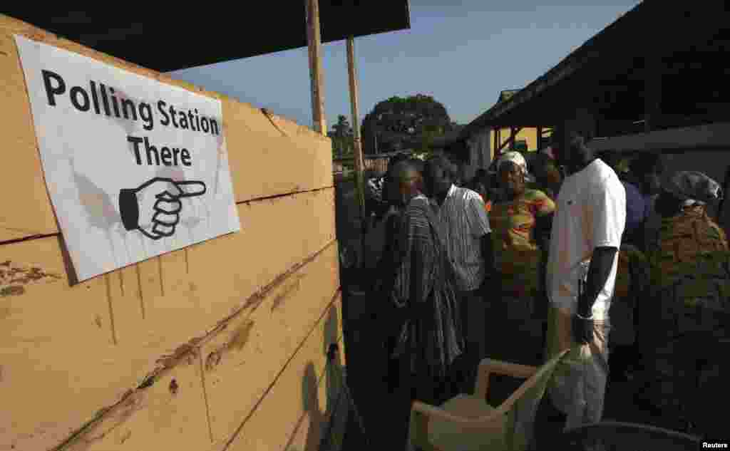 People wait to vote at a polling station in Kibi, eastern Ghana, December 7, 2012.