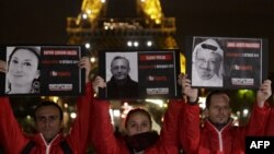 People hold portraits of killed journalists in front of the Eiffel Tower during an event organised by the Reporters Without Borders