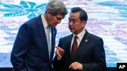U.S. Secretary of State John Kerry, left, and Chinese Foreign Minister Wang Yi chat after a group photo session before the East Asia Summit Foreign Ministers' Meeting in Kuala Lumpur, Malaysia, Aug. 6, 2015.