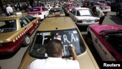 "FILE - A local taxi driver paints ""Uber out"" on the back window of his car during a protest in Mexico City, May 25, 2015."