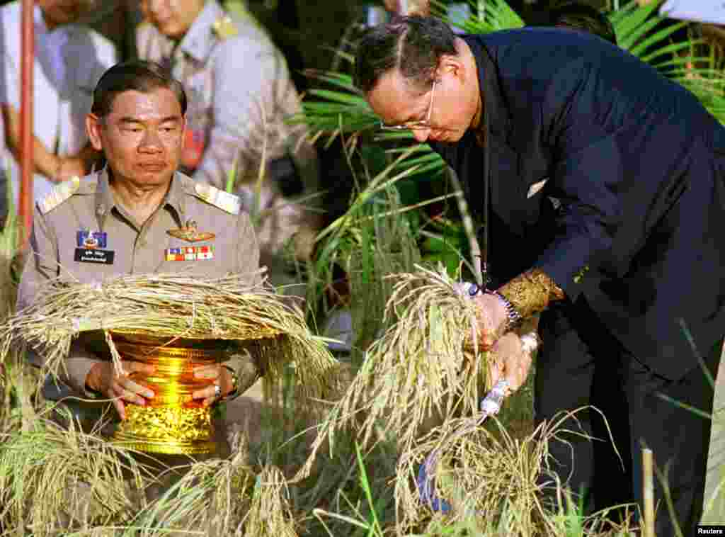 King Bhumibol Adulyadej (R) harvests rice at a project sponsored by the royal family in Prachinburi province about 100 kms east of Bangkok, Nov. 18, 1998. The 71-year-old king told local farmers that self-reliance would help them weather the country's most severe economic crisis in decades.