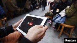 Seorang pria mencoba menonton YouTube dari tabletnya di sebuah kafe di Istanbul (27/3).