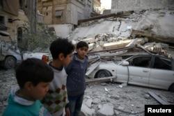 Djeca u blizini ruševina nakon vazdušnog napada na grad Dumu, u Istočnoj Guti, u blizini Damaska, Sirija, 6. februara 2018.