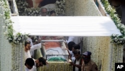 Husband Boney Kapoor, top, actors Anil Kapoor, third left and Arjun Kapoor, second left, stand beside as the body of Indian actress Sridevi covered with the Indian flag is carried in truck during her funeral in Mumbai, India, Wednesday, Feb. 28, 2018.