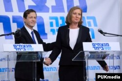 FILE - Isaac Herzog (L), leader of Israel's Labor party, and former Justice Minister Tzipi Livni shake hands after their joint news conference in Tel Aviv, Dec. 10, 2014.