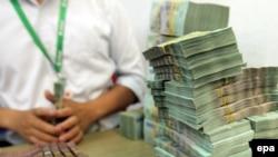 Tư liệu: Một nhân viên chuẩn bị tiền giấy cho thân chủ tại một ngân hàng ở Hà nội ngày 13/5/2015. EPA/MINH HOANG