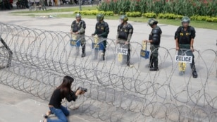 FILE - A Cambodian woman takes a photo of riot police standing behind bard wire at Freedom Park in Phnom Penh, May 1, 2014. U.S.-based Cambodian community activists are campaigning for a congressional resolution calling for human rights, democracy and the rule of law in Cambodia.