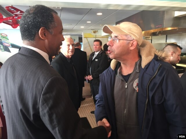Presidential candidate Dr. Ben Carson shakes the hand of a local resident at the Airport Diner in Manchester, New Hampshire, Feb 7, 2016. (K. Gypson/VOA)