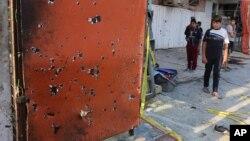 Warga setempat melihat tempat kejadian setelah terjadi ledakan di sebuah daerah komersial yang sibuk di Baghdad, Irak (13/7).