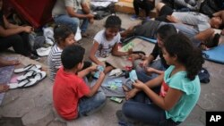 Children migrants play cards at an encampment set up by migrants near a Mexican immigration office in Matamoros, Mexico, Wednesday, July 31, 2019, on the border with the U.S. (AP Photo/Emilio Espejel)
