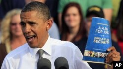 President Barack Obama holds up a copy of jobs plan during a joint campaign appearance with Vice President Joe Biden (not seen) at Triangle Park in Dayton, Ohio, October 23, 2012.