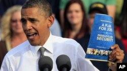 奥巴马总统在俄亥俄州代顿市的一次竞选造势集会上手持他的就业方案(2012年10月23日)