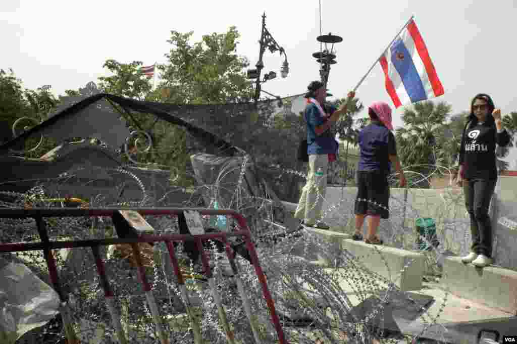 A woman poses on a downed barricade at the entrance to the government complex in Bangkok, Dec. 3, 2013. (Steve Herman/VOA)