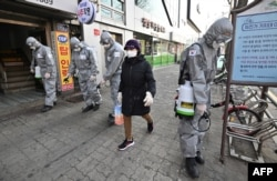 A woman wearing a face mask walks past South Korean soldiers wearing protective gear as they spray disinfectant on the street to help prevent the spread of the COVID-19 coronavirus, in Seoul on March 6, 2020.