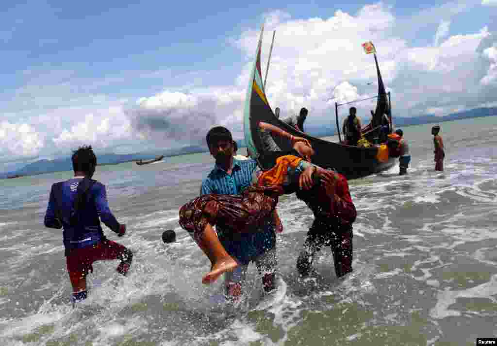 An exhausted Rohingya refugee woman is carried to the shore after crossing the Bangladesh-Myanmar border by boat through the Bay of Bengal, in Shah Porir Dwip, Bangladesh.