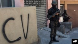 "FILE - A soldier stands guard next to a wall tagged with the acronym ""CV"" identifying the criminal organization ""Comando Vermelho"" or Red Command, during an operation at the Rocinha slum, in Rio de Janeiro, Brazil, Oct. 10, 2017."