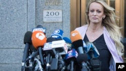 Adult film actress Stormy Daniels approaches the microphones set up outside federal court to address reporters, April 16, 2018, in New York.