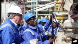Ghanaian President John Atta Mills (2nd R) turns a valve at FPSO Kwame Nkrumah oil rig at the Jubilee field in Takoradi, 15 Dec 2010