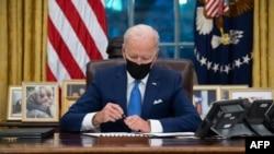 Presidente americano Joe Biden assinando ordens executivas relacionadas com imigração