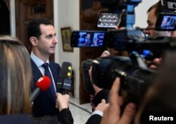 FILE - Syria's President Bashar al-Assad speaks to journalists in Damascus, Syria, Jan. 9, 2017. Iraqi firebrand cleric Moqtada al-Sadr is calling on Assad to resign to help Syria avoid the menace of war and dominance of terrorists.