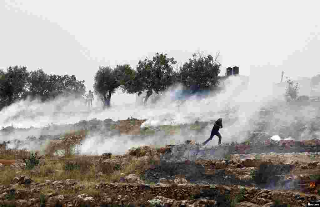 Seorang warga Palestina lari dari gas air mata yang ditembakkan oleh tentara Israel di Ramallah, Tepi Barat.
