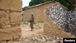 FILE - A United Nations peacekeeper stands among houses destroyed by violence in the abandoned village of Yade, Central African Republic, April 27, 2017.