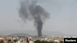FILE - Smoke rises from a snack food factory after a Saudi-led air strike in Sana'a, Yemen. Aid group Doctors Without Borders said the strike in Haydan hit a school and wounded another 28 people, and that all of the victims were between 8 and 15 years old.
