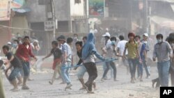 FILE - Cambodia garment workers throw stones at riot police during a strike near Phnom Penh, Cambodia, Friday, Jan. 3, 2014. (AP Photo/Heng Sinith)