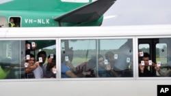 一群寻求庇护者在巴布亚新几内亚的机场降落后出示他们的身份证(资料图)