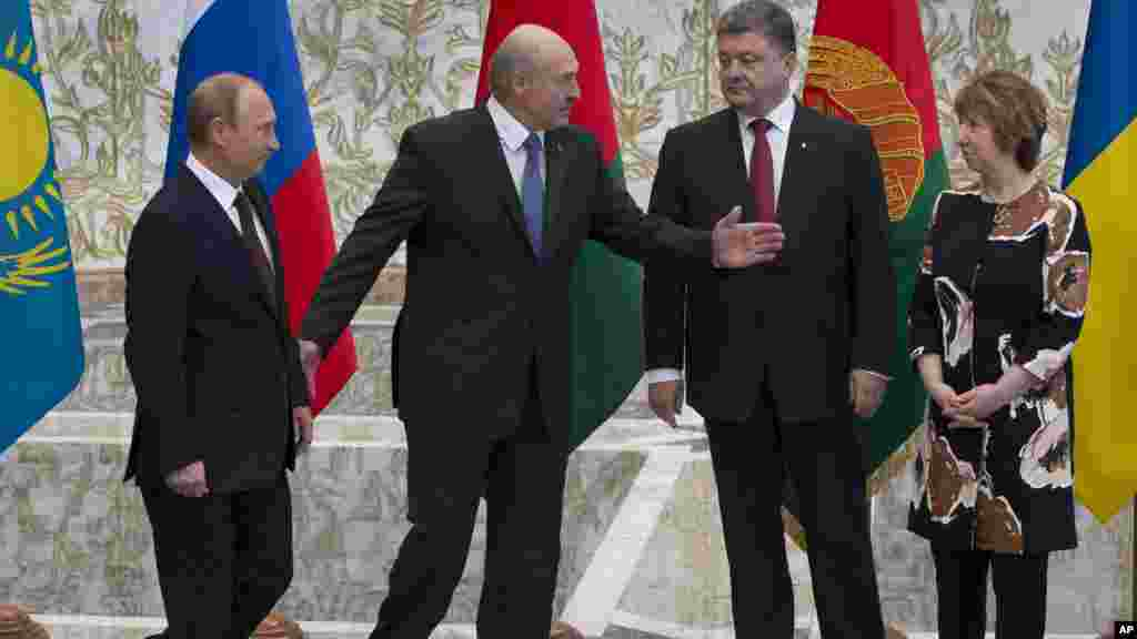 Belarusian President Alexander Lukashenko, second left, welcomes Russian President Vladimir Putin, left, Ukrainian President Petro Poroshenko, second right, and EU foreign policy chief Catherine Ashton, right, to their talks after after posing for a phot