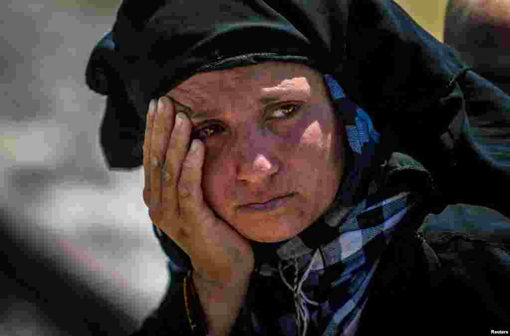 A woman reacts as she rests from walking back to Tel Abyad town, Raqqa governorate, after fleeing Maskana town in the Aleppo countryside, Syria, June 16, 2015.
