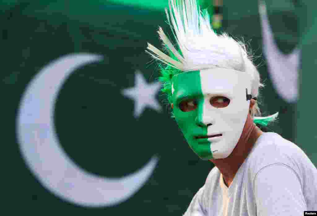 A vendor wears a mask with the colors of the Pakistani flag at a roadside stall in Islamabad as people prepare to celebrate the country's Independence Day on August 14 at a roadside stall in Islamabad.