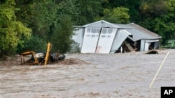 Overflowing St. Vrain River swamps structure and piece of heavy machinery following overnight flash flooding near Lyons, Colorado, Sept. 12, 2013.