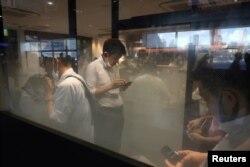 Orang-orang memeriksa ponsel mereka di ruang merokok di Stasiun Shinagawa di tengah pandemi COVID-19 di Tokyo, Jepang, 2 Agustus 2021.