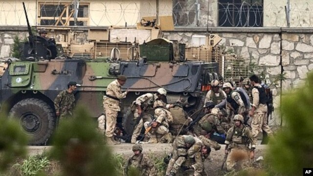 NATO and Afghan troops attend to casualties during a battle with Taliban insurgents who took over a building near the U.S. embassy in Kabul September 14, 2011.