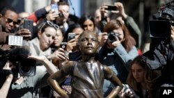 FILE - People stop to photograph the Fearless Girl statue in New York, March 8, 2017.
