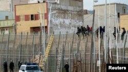 Des migrants africains sont assis au sommet d'une clôture de la frontière entre le Maroc et l'Espagne, le 10 février 2015. (Reuters/Jesus Blasco de Avellaneda)