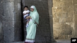 An Indian Muslim woman holds her child as she walks out of Jerusalem's Old City after Friday prayers