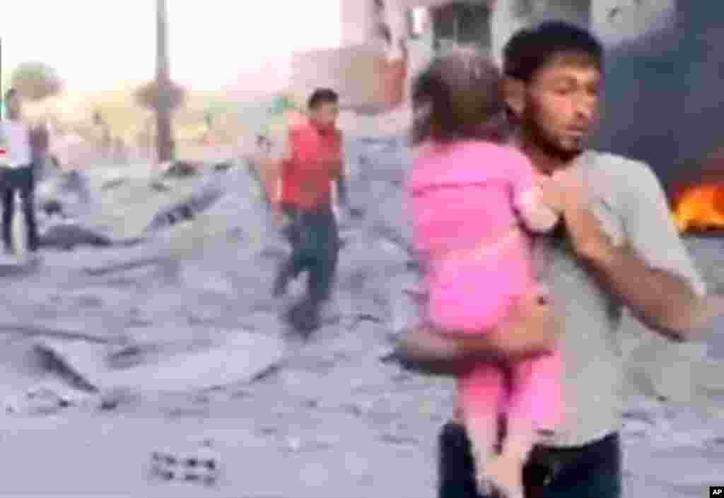 This image taken from video obtained from the Shaam News Network shows a Syrian man carrying an injured child away from a missile strike in Raqqa, Syria, August 7, 2013.