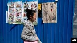 중국 베이징 시내에 붙어있는 외국인 간첩에 대한 경고 포스터 앞으로 시민이 걸어가고 있다. (자료사진)