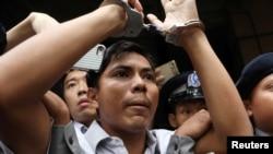 سزا پانے والے صحافی کیو سوئی او کو پولیس عدالت سے لے جا رہی ہے۔
