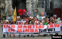 Activists display a banner and a mural of President Rodrigo Duterte to denounced the declaration of martial law in Mindanao island, one year after Islamic militants occupied parts of the southern Philippine city of Marawi during a protest in Manilla.