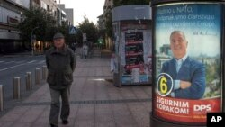 "A man walks by an election poster of pro-Western Prime Minister Milo Djukanovic, leader of the Democratic Party of Socialists, reading ""We are joining NATO, we are at the doorstep at the developed European family"" and ""With firm step ahead!"" in downtown Podgorica, Montenegro, Oct. 12, 2016."