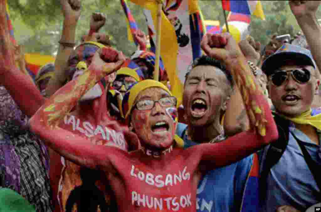 Exile Tibetans, with painted bodies and names of monks who self-immolated themselves, shout slogans in a protest march in New Delhi, India, Friday, Oct. 21, 2011.