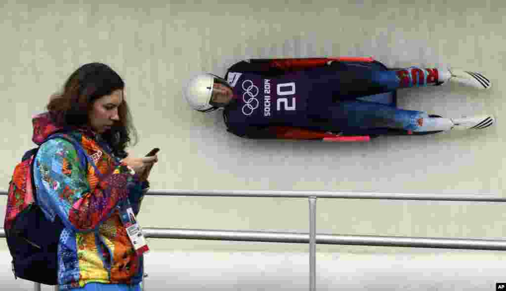 Natalja Khoreva of Russia takes a turn as a volunteer looks at her cell phone during the women's singles luge training, Krasnaya Polyana, Russia Feb. 9, 2014.