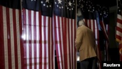 ووٹر پولنگ بوتھ میں اپنا ووٹ ڈال رہے ہیں۔